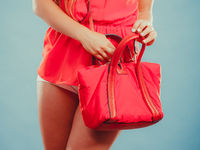 Closeup of fashion woman with red handbag.
