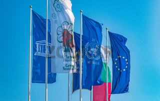 The Flags of European Union, United Nations, Unesco, Bulgaria, and Nessebar city waving in the wind. EU, UN, Unesco, Bulgaria, and Nessebar flags against a blue sky