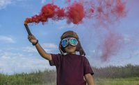 Little boy plays with colored smoke, wearing a 1920s aviator hat and airplane pilot glasses