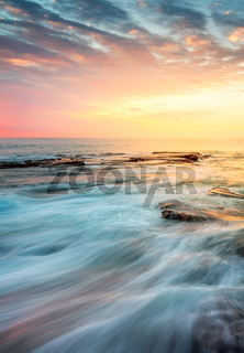 Incoming waves wash over rocks at sunrise