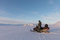 Svalbard, Norway - March 2019: Man standing next to a Yamaha snowmobile in arctic landscape at Svalbard