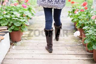 Woman's legs in boots walking along wooden path