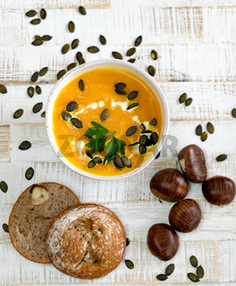 organic pumpkin soup in a white bowl framed by chestnuts and chestnut bread and pumpkin seeds