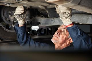 KFZ Mechaniker bei Auto Reparatur unter dem Auto