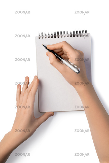 Woman's holding pen and writing in notebook