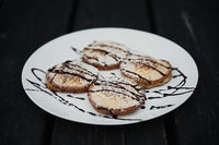 homemade chocolate pancakes served on a white plate over black texture background