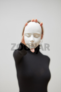 Plaster mask in the hand of young female instead face on a white background, place for text. Concept The masks we wear.