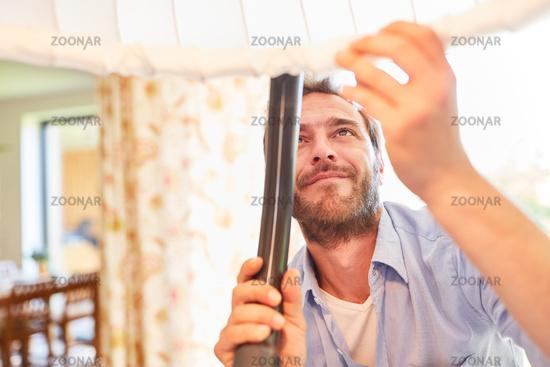 Hausmann beim Staubsaugen an einer Hängelampe