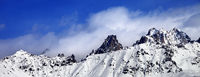 Snow avalanches mountainside in clouds