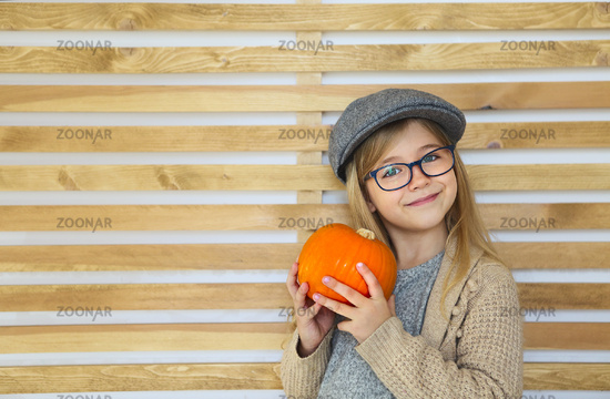 Happy little girl with autumn pumpkin by the wooden wall background