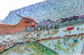 Mosaic as a ceramic or ceramic mosaic. The man organizes design with a tweezers a puzzle of ceramic