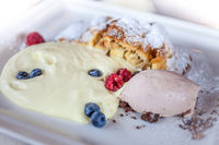 Apple strudel with vanilla sauce and berries