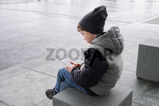 candid photo of young boy with smartphone outdoors in winter