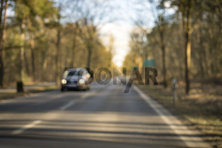 blurry street with car and forrest for backgrounds
