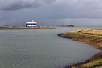 Entrance Dutch canal Terneuzen and cargo ship sailing river Schelde