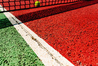 Background of a tennis net with a ball on the other side out of focus, soil texture.