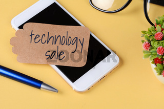 Paper card with 'technology sale' text and pen, glasses with phone
