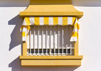Spanish Window with white and yellow awning
