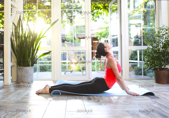 Young brunette woman in a sporty uniform doing yoga on the terrace