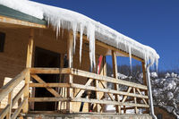 Wooden house with big icicles on roof and ski equipment on balcony