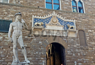 Florence, Italy - June 13, 2019:  replica statue of David by Michelangelo in front of Palazzo Vecchio of Florence
