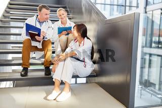 Junges Ärzteteam in einer Pause im Treppenhaus