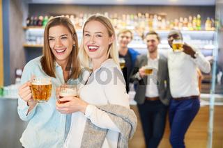 Zwei Freundinnen feiern ausgelassen mit Bier