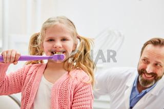 Mädchen und Kinderzahnarzt mit riesiger Zahnbürste