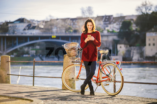 theme tourism on bicycle and modern technology. Beautiful young caucasian woman stands near red retro bicycle on riverside river Rhine Basel Swiss winter warm sunny weather uses the phone in hand