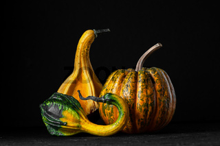 Three decorative pumpkins on a black background.