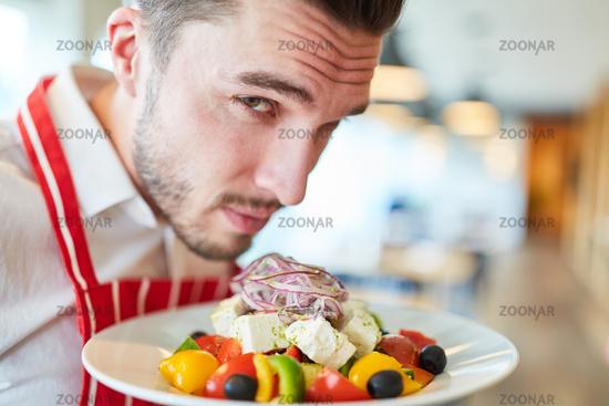 Kellner serviert Griechischen Salat als Vorspeise