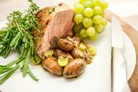 Closeup of delicious one piece roasted pork shoulder with roasted garlic, grapes, figs, and fresh rosemary.