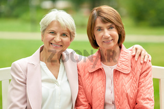 senior women or friends sitting on bench at park