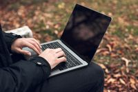 Young man sitting on park bench on autumn with laptop. Student using computer outdoors. Close up.