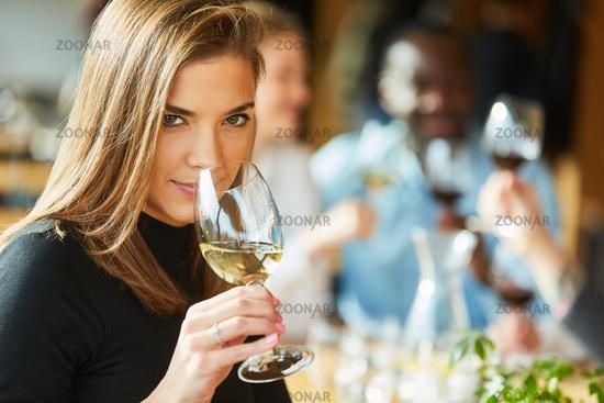 Junge Frau mit Freunden bei einer Weinprobe