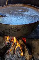 Old wood burning stove with big pan preparing beans