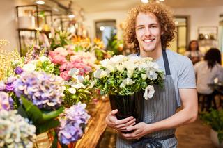Mann als Florist zwischen frischen Schnittblumen