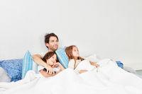 Vater und glückliche Kinder morgens im Bett