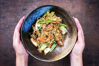 Traditional stir-fried Thai phat phak kung with mie noodlesas top view in a bowl in woman hands