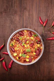 Chili con carne and chilli peppers, shot from the top on a dark rustic wooden background with a place for text
