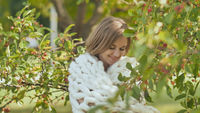 A smiling girl wrapped in a merino plaid in the middle of a cherry tree in a park in early autumn.