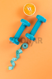 Dumbbells, a centimeter and half an orange on a light orange background.