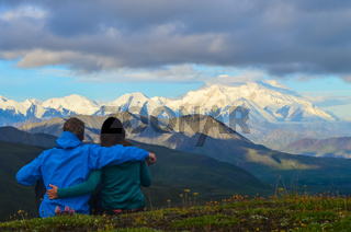 Couple watching a morning view of Mount Denali (mt Mckinley) peak during golden hour from Stony Dome overlook. Denali National Park and Preserve, Alaska, United States