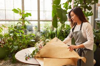 Asiatische Floristin wickelt Blumenstrauß in Papier