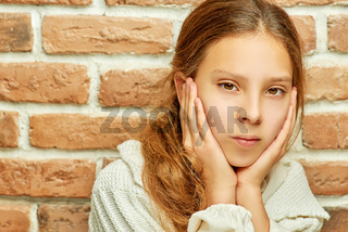 Girl teenager with long hair looks thoughtfully
