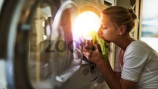 Frau riecht an Kleidung aus dem Wäschetrockner
