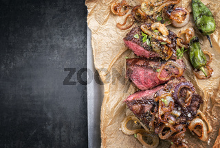 Traditional German barbecue sliced zwiebelrostbraten with fried onion rings and green paprika as top view on backing paper in a skillet with copy space left