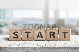 Start sign in a bright office on a wooden table