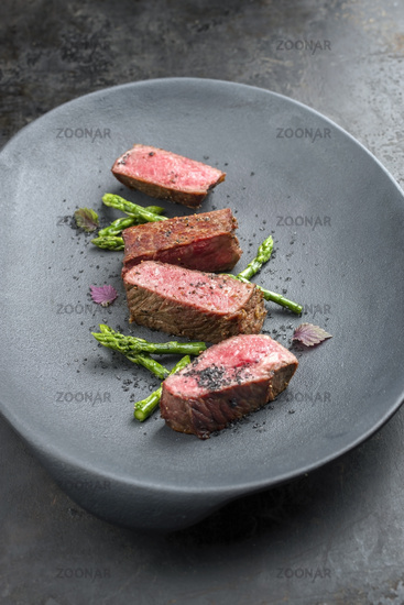 Barbecue dry aged wagyu fillet steak with blanched green asparagus tips and herbs as closeup on a modern design plate with copy space