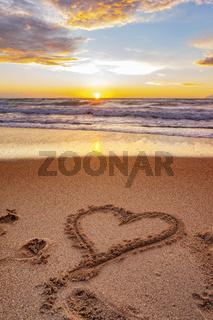 Herz im Sand bei Sonnenuntergang
